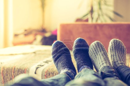 Feet with woollen socks in the wintertime: Couple is relaxing on the couch