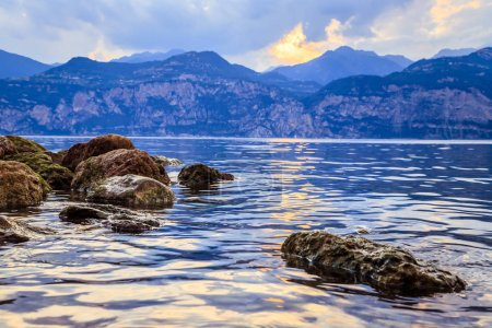 Photo for Colorful rocks and reflections in the lake Lago di Garda. Clear water, mountains and sky. - Royalty Free Image