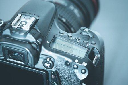 Photo pour Appareil photo reflex professionnel avec téléobjectif sur la table, découpe, fond flou - image libre de droit