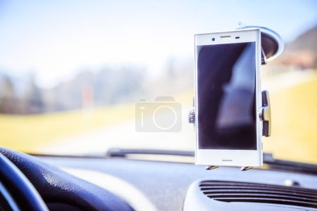 Photo for Interior of a modern car on a sunny day. Smartphone on mobile mount, used as navigation device - Royalty Free Image