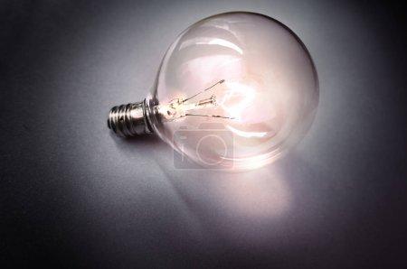 Photo pour Ampoule ides éclairée sur fond gris - image libre de droit