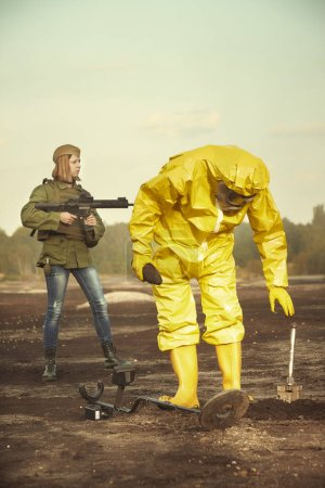 Photo for Specialist in chemical protective suit localizing and pick up artillery grenade on field - Royalty Free Image