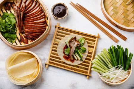 Sliced Peking Duck in bamboo steamer served with fresh cucumber, onion, Hoysin sauce and roasted wheaten pancakes on white wooden background