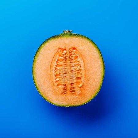 Photo pour Demi-coupe de melon cantaloup mûr sur fond bleu - image libre de droit