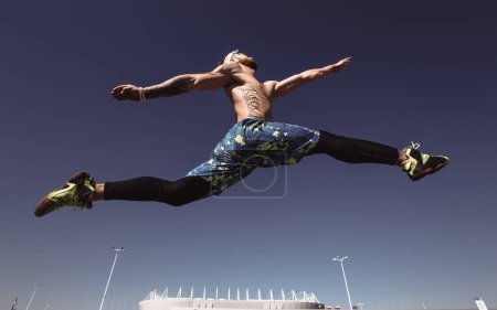 Photo for Young athletic man with a naked torso with headband dressed in the black leggings and blue shorts is jumping high on the background of the stadium and blue sky on a warm sunny day . - Royalty Free Image