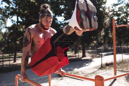 Photo for Young man in headband with naked torso dressed in black leggings and red shorts doing press exercises on the horizontal bar on the sports ground outside on a sunny day . - Royalty Free Image