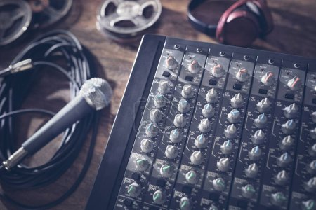 Photo for Sound recording studio mixer desk with microphone, headphones and reel tape - Royalty Free Image