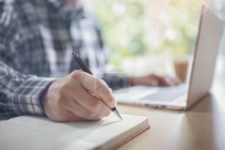Photo pour Homme d'affaires, écrivant à son bureau au bureau avec un ordinateur portable - image libre de droit