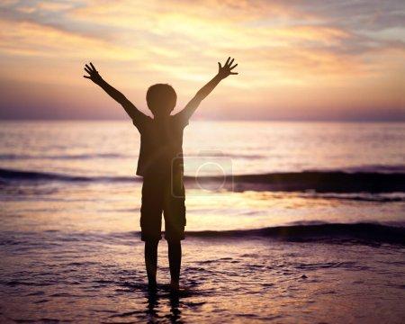 Photo pour Silhouette d'un garçon avec les mains levées au coucher du soleil sur la mer concept de religion, culte, prière et louange - image libre de droit