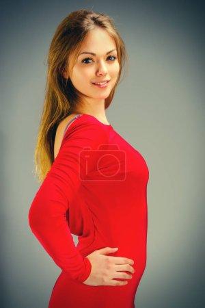 Photo pour Portrait d'une belle jeune femme blonde avec ses cheveux dans une robe rouge - image libre de droit