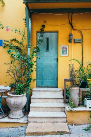 Bright yellow house with plants