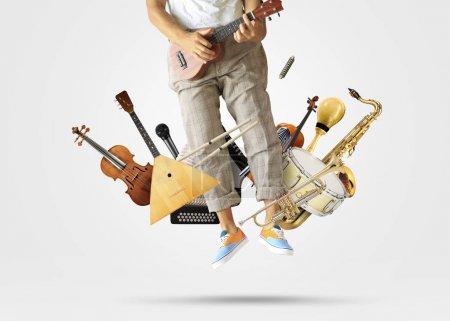 Photo pour Jeune homme a sauté jouer de la guitare parmi les instruments de musique - image libre de droit