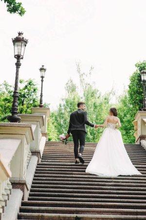 Photo pour Marié et marié marchant dans les escaliers du parc - image libre de droit
