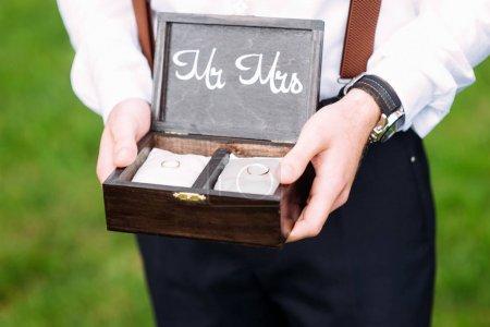 Best man détient une boîte en bois avec des alliances en or sur des oreillers blancs. Cérémonie de mariage d'été. Mariage rustique. Monsieur et Madame .