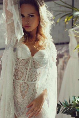 Photo pour Belle sensuelle jeune femme blonde qui pose en lingerie blanche. Idéal corps mince sexy. Fille avec long cheveux bouclés - image libre de droit