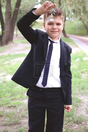 Photo for Schoolboy looks at the globe and dreams in nature - Royalty Free Image