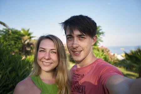 Mann und Frau machen ein Selfie auf einem Hintergrund von Palmen und