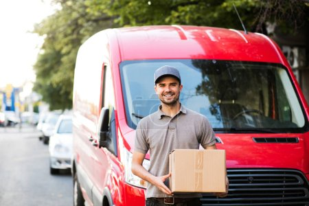 your shipping is here. happy delivery man in grey shirt with cap standing with his cardboard box on the street looking to camera with smile, in front of his delivery car
