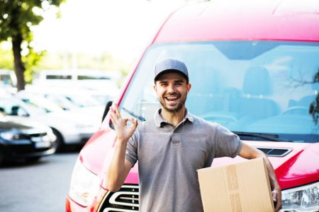 your shipping is here. happy delivery man in grey shirt with cap standing with his cardboard box on the street looking to camera with smile showing confidence, in front of his delivery car