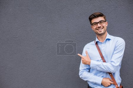 Photo for Pointing the empty side. handsome smart casual man with eyeglasses and leather bag outside pointing a free space next to him with confidence and smile - Royalty Free Image
