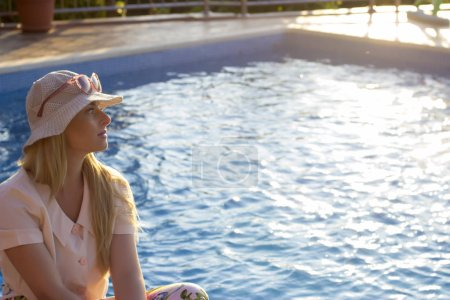 Young woman relaxing at poolside on summer vacatio...
