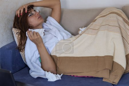Photo for Woman Caught Cold. Sitting On The Sofa. Headache. Virus. Upset Young Woman Suffering From Influenza At Home. Sick Young Woman At Home On The Sofa With A Cold, Covering With A Blanket - Royalty Free Image