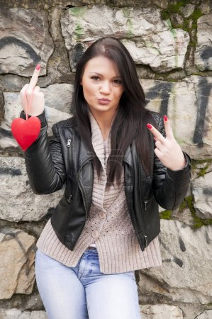 Photo pour Attractive girl in leather jacket holding a red heart and showing finger signs - image libre de droit