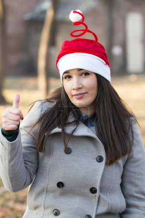 Photo for Portrait of beautiful brunette in grey coat and santa claus hat showing thumbs up in public park - Royalty Free Image