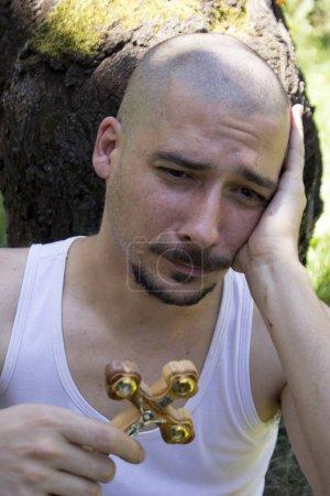 Photo pour Le jeune homme barbu désespéré tient la croix d'or et prie pour des temps meilleurs. Concept de foi, de spiritualité et de religion. - image libre de droit