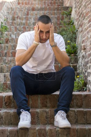 Photo for Outdoor portrait of sad young man covering his face with hands sitting on stairs. Selective focus on hands. Sadness, despair, tragedy concept - Royalty Free Image