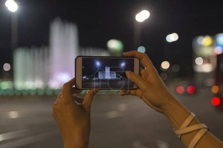 Photo for Young woman takes photos using smart mobile cell phone camera of a dancing fountain in Belgrade - Royalty Free Image