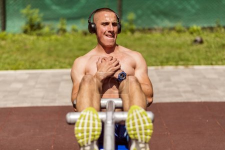 Photo for Young Muscular Man With Headphones in Perfect Body Shape Doing Sit Ups in Public Park - Royalty Free Image