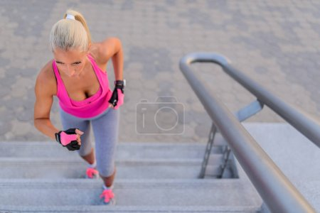 Photo for Young sport woman running upstairs on city stairs - Royalty Free Image