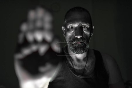 Photo for Man, guy, hipster, making stop sign, showing rejective hand gesture, on the black backround, stop war, serious look, looking at the camera - Royalty Free Image