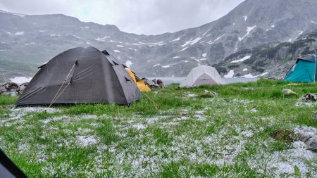 Photo pour Tentes sous la grêle et la pluie froide en été, midi au lac Bucura, montagnes Retezat. Vue de l'intérieur d'une tente, avec beaucoup de grêlons dans l'herbe verte. Conditions météorologiques difficiles dans les montagnes . - image libre de droit