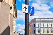 "Постер, картина, фотообои ""Info sign with a forward/up arrow on a street pole, with city architecture in the back."""