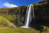 Wonderful view of Seljalandsfoss Waterfall in Iceland. Sunlight day in summer with rainbow and green landscape. Famous landmark on the route number one.