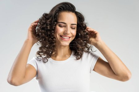 cheerful girl with curly hair smiling isolated on grey