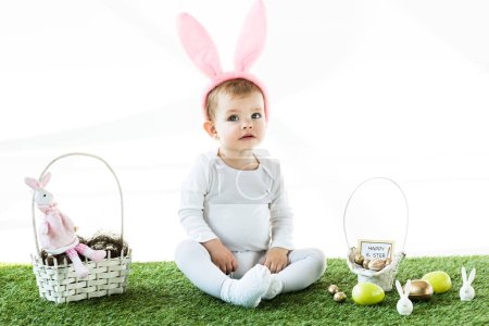 Photo pour Mignon bébé dans les oreilles de lapin bandeau assis près des paniers de paille avec des œufs colorés de Pâques et des lapins décoratifs isolés sur blanc - image libre de droit