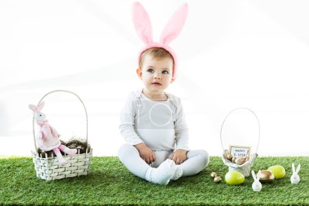 Photo pour Adorable enfant dans les oreilles de lapin bandeau assis près des paniers de paille avec des œufs colorés de Pâques et des lapins décoratifs isolés sur blanc - image libre de droit