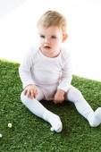 """Постер, картина, фотообои """"очаровательны блондинка ребенок сидит на зеленой траве изолированы на белом"""""""