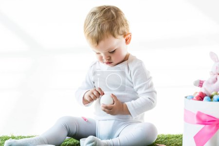 Photo for Adorable child holding white chicken egg while sitting near box with Easter eggs isolated on white - Royalty Free Image