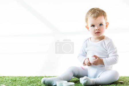Photo for Adorable baby sitting on green grass near white bowls and holding chicken egg isolated on white - Royalty Free Image