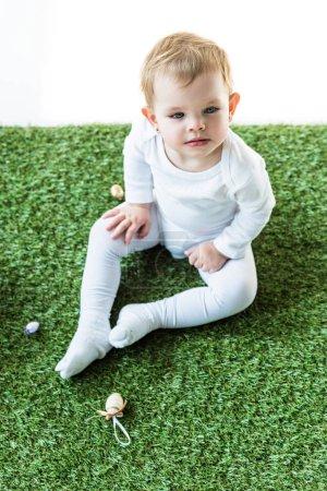 Photo pour Enfant blond mignon s'asseyant sur l'herbe verte et regardant loin isolé sur le blanc - image libre de droit