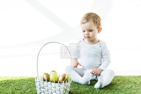 Photo for Cute child sitting near straw basket with colorful Easter eggs isolated on white - Royalty Free Image