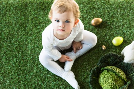 top view of adorable child looking at camera while sitting near Easter eggs, decorative rabbit and savoy cabbage
