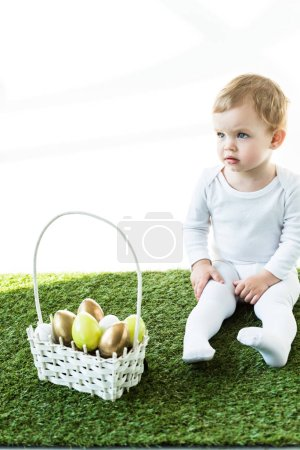 Photo for Cute kid sitting near straw basket with colorful Easter eggs isolated on white - Royalty Free Image