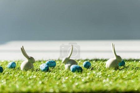 Photo pour Foyer sélectif de lapins décoratifs et oeufs de cailles bleues sur la surface de tapis d'herbe verte - image libre de droit