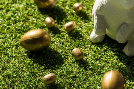 Photo for Shiny Easter eggs and decorative rabbit on green grass surface - Royalty Free Image