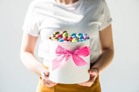 Photo for Cropped view of woman holding round box full of colorful Easter eggs isolated on grey - Royalty Free Image